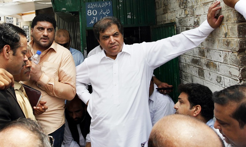 PML-N leader Hanif Abbasi talks to his supporters outside a court in Rawalpindi. —AP