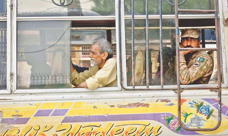 ARMY personnel accompany polling staff in a minibus as preparations for elections reach their final stages in the city on Tuesday.—Fahim Siddiqi / White Star