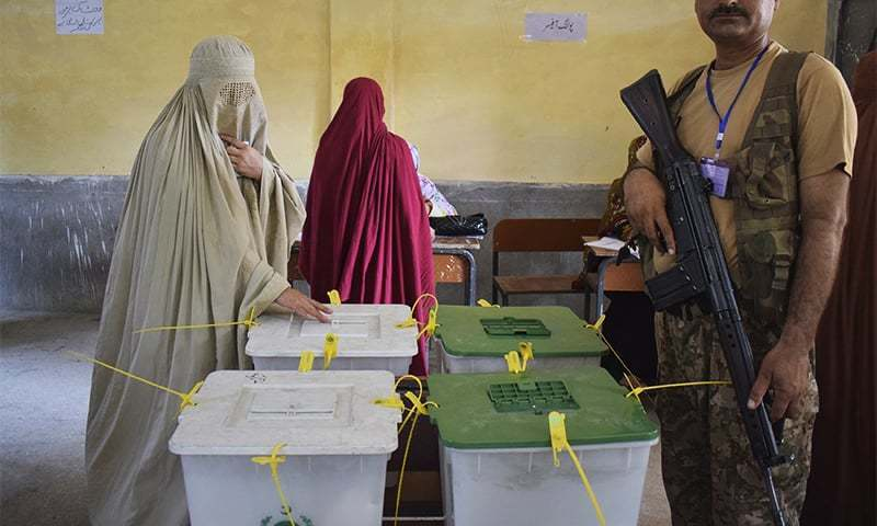 A woman casts her vote at a polling station in Peshawar. ─ AP
