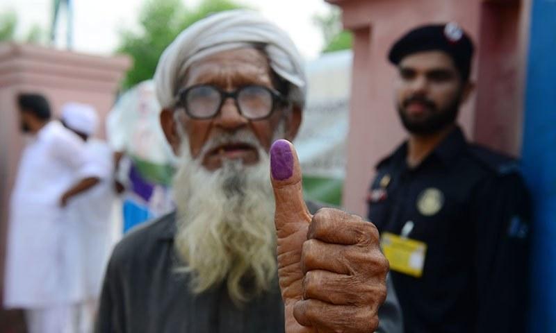 بزرگ شہری لاہور میں اپنا ووٹ کاسٹ کرنے کے بعد انگوٹھے کا نشان دکھاتے ہوئے—فوٹو: اے پی