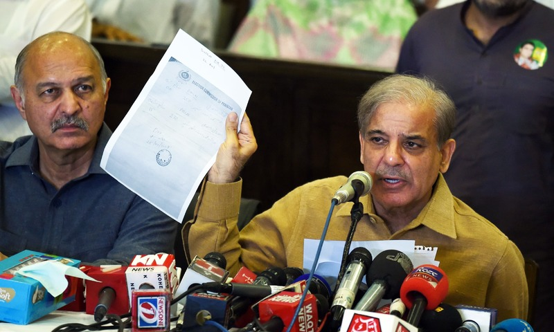 PML-N Shahbaz Sharif shows a document as he speaks during a press conference at his political office in Lahore. —AFP