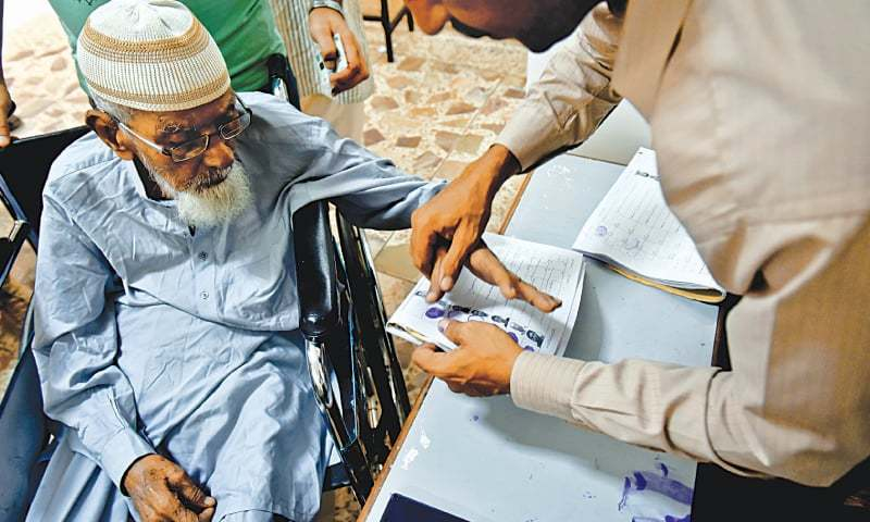 LAW enforcers frisk voters outside a polling station in Azizabad while (right) an elderly voter is helped to complete the formalities before casting his ballot in a Gulshan-i-Iqbal polling facility on Wednesday.—Fahim Siddiqi / White Star