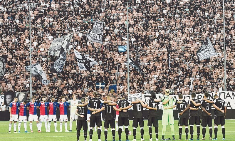 THESSALONIKI: Players of FC Basel (L) and Paok Thessaloniki stand during a minute's silence for the victims of fires in Greece during their Champions League second qualifying round match at the Toumba Stadium.—AFP