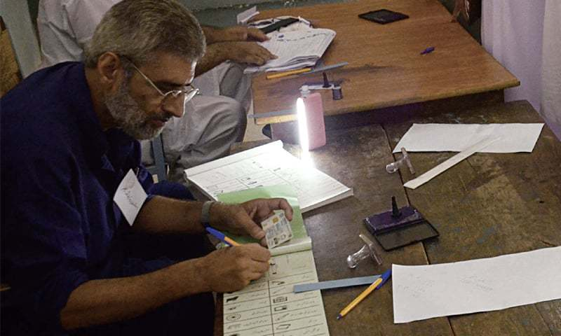 A presiding officer works in the light of a torch due to loadshedding at a polling station in NA-132. — Online