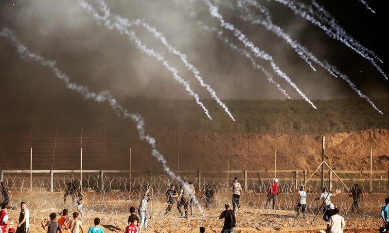 Palestinian protesters gather as tear gas canisters are launched by Israeli forces during a demonstration along the border between Israel and the Gaza strip. —AFP