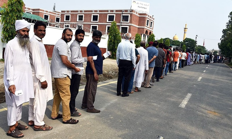 APP16-25 LAHORE: July 25 – Voters standing in queue to cast their ballots outside polling station for NA-135 and PP-161 constituencies at City School Johar Town. APP photo by Chaudhry Ansar