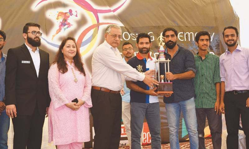 KARACHI: Pakistan's prolific middle-order batsman Asad Shafiq and SMC Principal Professor Ghulam Sarwar Qureshi jointly present the winners trophy to SMC's boys futsal team at the closing ceremony of  the JSMU event as Chairperson Students Council  Dr Ghazala Usman and others look on. —Photo by Tahir Jamal