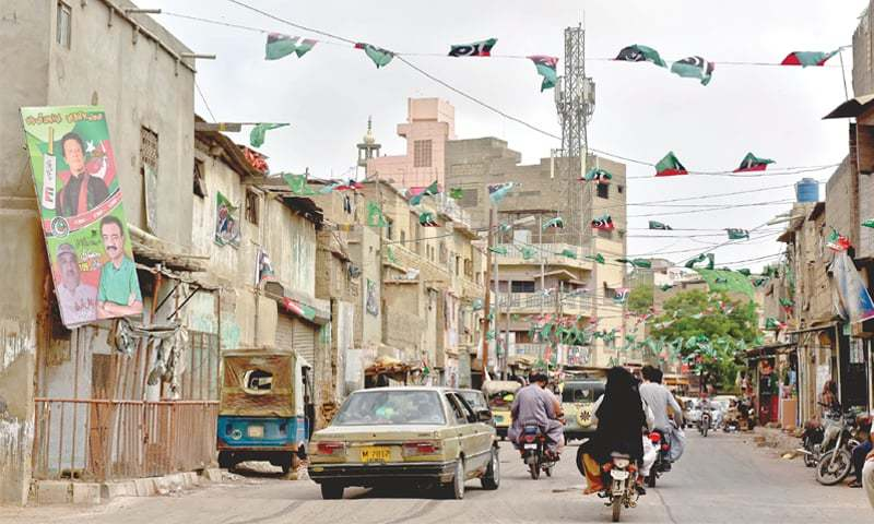 A BUSY road in Bhempura locality of Lyari with flags and posters of major political parties.—Fahim Siddiqi / White Star