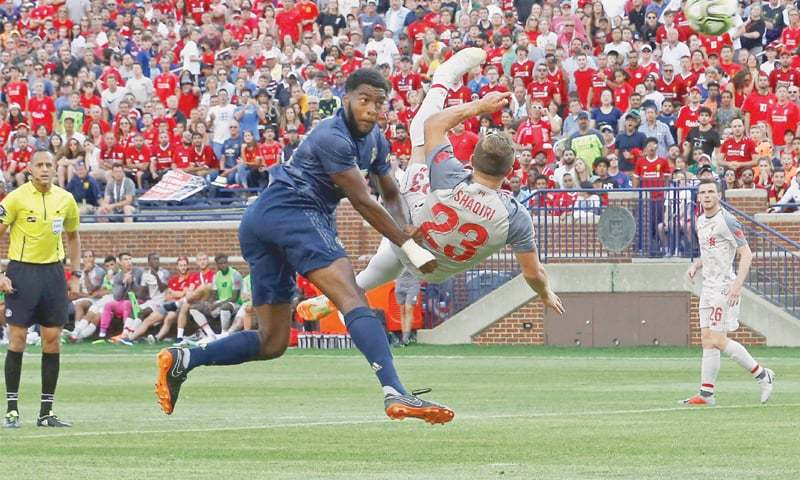ANN ARBOR (Michigan): Liverpool's Xherdan Shaqiri (R) shoots to score with an overhead kick during the International Champions Cup match at the Michigan Stadium.—AFP