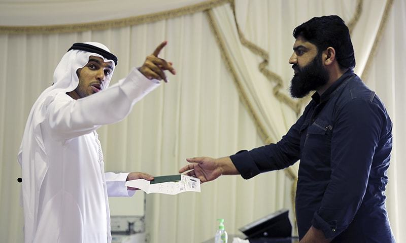 A government employee, left, directs a foreign worker at a visa processing center in Al Aweer, about 30kms east of Dubai, United Arab Emirates, on Wednesday. — AP