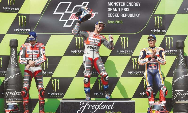 BRNO: Ducati's Andrea Dovizioso (C) celebrates on the podium alongside team-mate and runner-up Jorge Lorenzo (L) and third-placed Marc Marquez of Repsol Honda after the Czech Republic MotoGP on Sunday.—Reuters