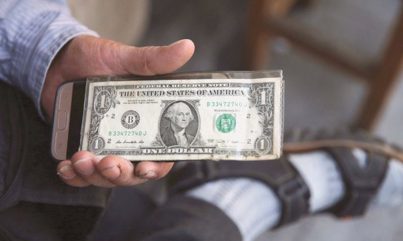 In this July 30 photo, an Iranian street money exchanger holds a US banknote in downtown Tehran, Iran.—AP