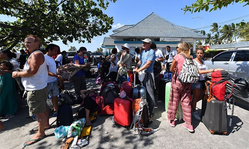 Foreign tourists wait for transportation after arriving from the nearby Gili islands at the port in Bangsal northern Lombok island on August 6. ─ AFP