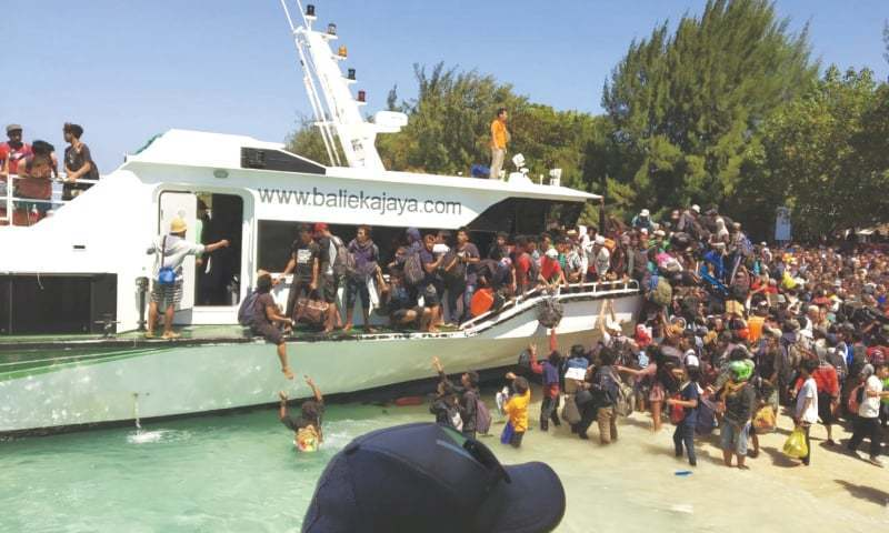 TOURISTS affected by the earthquake struggle to board a boat as they are evacuated to the main island of Lombok in Indonesia on Monday.—AP