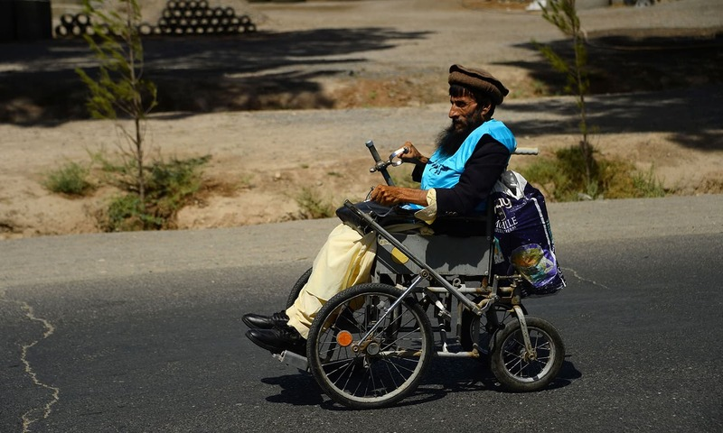 An Afghan amputee marches on his wheelchair with others (unseen) to demand an end to the war. —AFP