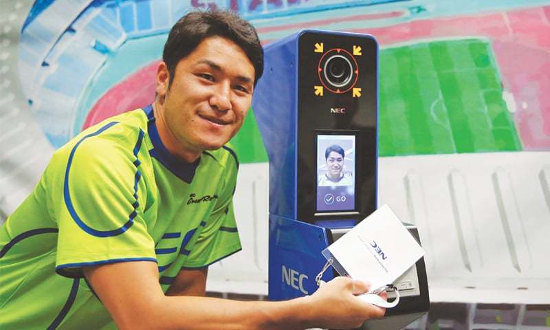 TOKYO: NEC Green Rockets' rugby player Teruya Goto poses with the face recognition system for Tokyo Olympics and Paralympics, which is developed by NEC corp, during its demonstration on Tuesday.—Reuters