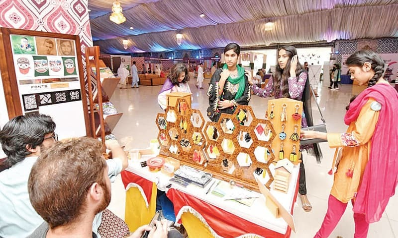 Visitors at a stall at the exhibition in Peshawar on Tuesday. — Dawn