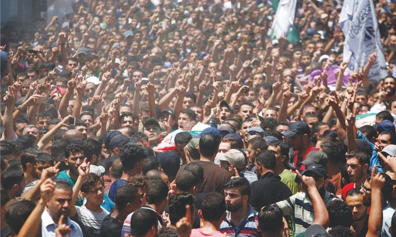 Jabaliya (Gaza Strip): Mourners carry the body of a Hamas member who was killed in Israeli tank shelling on Tuesday.—Reuters