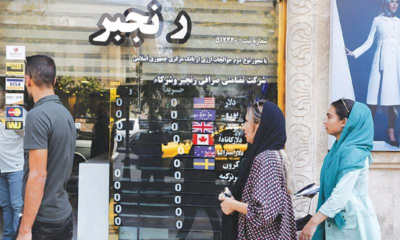 PEOPLE walk in front of a currency exchange shop in Tehran on Wednesday.—AFP