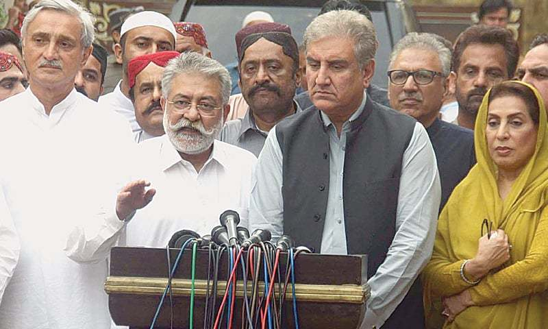 KARACHI: Grand Democratic Alliance chief Pir Pagara talks to reporters along with senior Pakistan Tehreek-i-Insaf leaders Shah Mehmood Qureshi and Jahangir Tareen outside Kingri House on Thursday.—Online