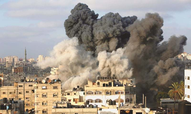 Gaza City: Smoke rises after an Israeli aircraft bombed a multi-storey building on Thursday.—Reuters