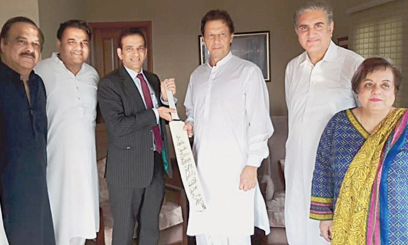 ISLAMABAD: Indian High Commissioner Ajay Bisaria presents a cricket bat which carries signatures of Indian players to PTI chairman Imran Khan after a meeting at Mr Khan's Banigala residence on Friday.—White Star