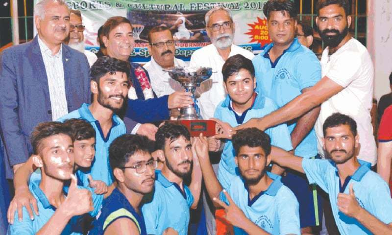KARACHI: Metropolitan Commissioner Dr Saifur Rahman presents the winner's trophy to Quaid-i-Azam XI basketball team on Friday.