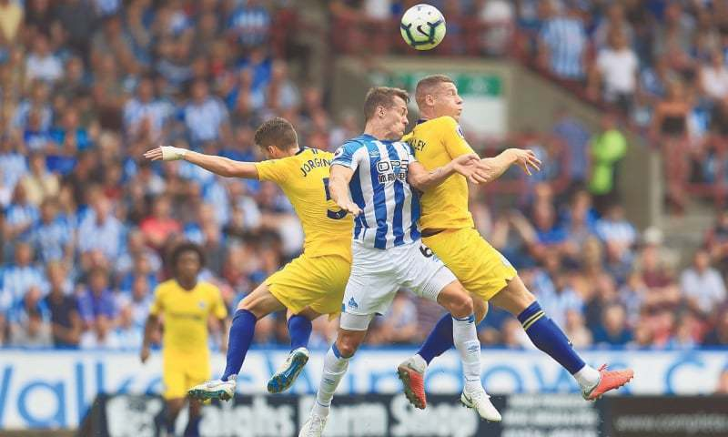 HUDDERSFIELD: Huddersfield Town's Jonathan Hogg (C) battles with Chelsea's Jorginho (L) and Ross Barkley during their English Premier League match at the John Smith's Stadium on Saturday.—AP