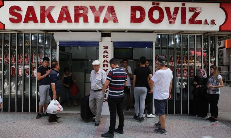 ANKARA: People look at foreign exchange rates on Friday. Turkish President Recep Tayyip Erdogan called on Turks to support their struggling currency, the lira, by exchanging any foreign money, saying Turkey faces an economic war.—AFP