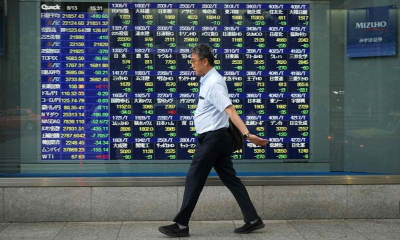 Tokyo: A pedestrian walks past a stock indicator board for the Tokyo Stock Exchange on Monday. Tokyo's benchmark Nikkei index dropped nearly two per cent as Turkey's lira plunged on tensions between Ankara and Washington, fanning fears of possible wider financial instability.—AFP