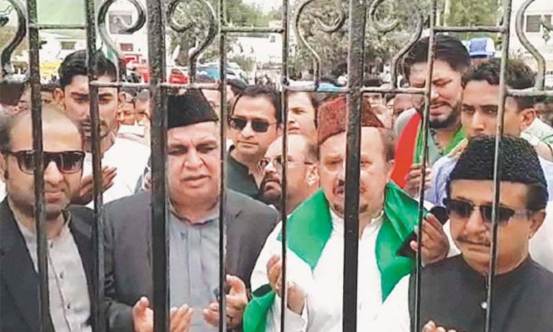 GOVERNOR-designate Imran Ismail, accompanied by other PTI leaders, offers Fateha outside the Quaid's mausoleum after being denied entry to the mazar grounds.—PPI