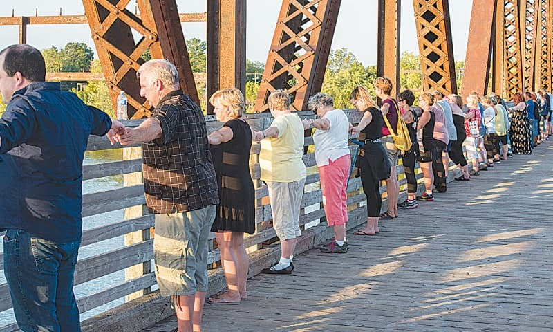 FREDERICTON: Thousands of people remember last week's shooting victims by joining hands on the Bill Thorpe Walking Bridge in New Brunswick, Canada, on Monday.—AP