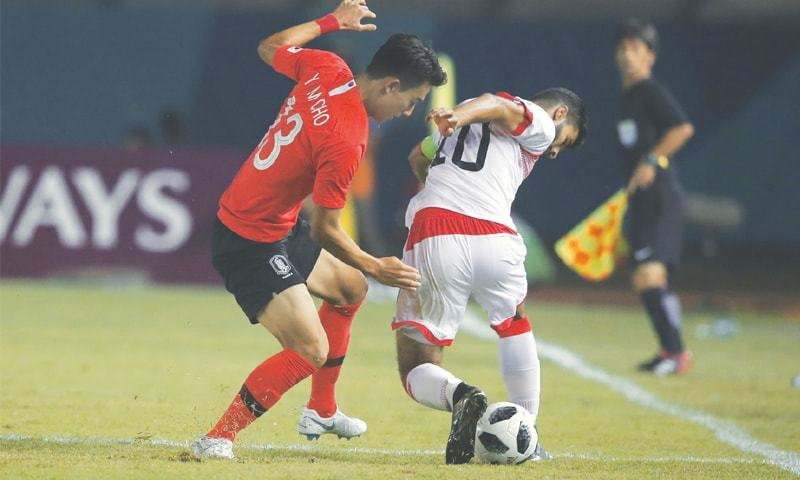 BANDUNG: South Korea's Yumin Cho (L) vies for the ball with Bahrain's Mohamed Hardan during the Asian Games group 'E' match at the Si Jalak Harupat Stadium on Wednesday.—AP