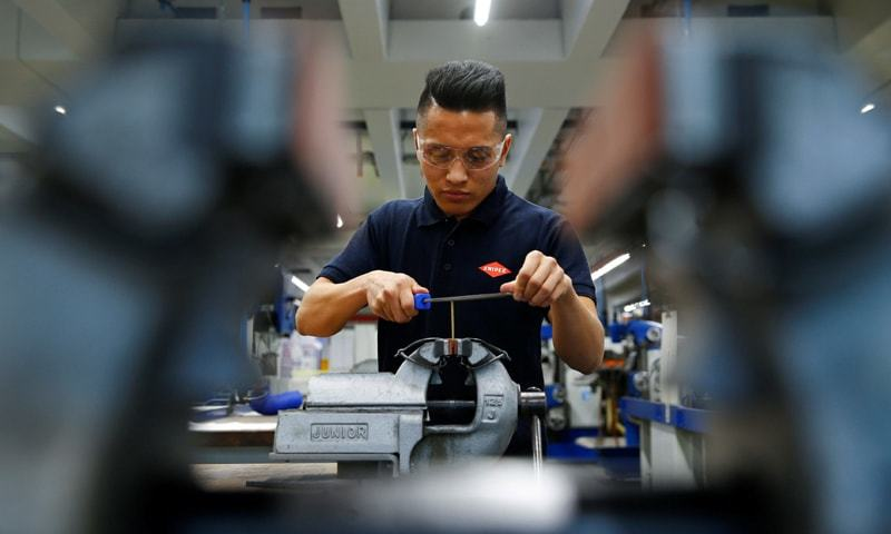 Wuppertal (Germany): Ahmad Hosseini, 18-year-old trainee and former refugee from Afghanistan poses for an image next to a computerised CNC miller at the training workshop of Knipex, a 130 year-old family-owned pliers and tools maker company —Reuters file photo