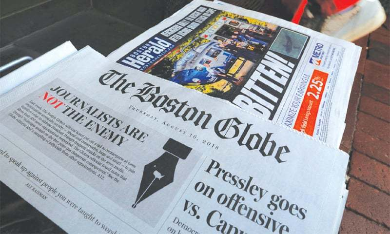 Cambridge (Massachusetts): A customer walks past the front page of The Boston Globe newspaper referencing their editorial defence of press freedom.—Reuters