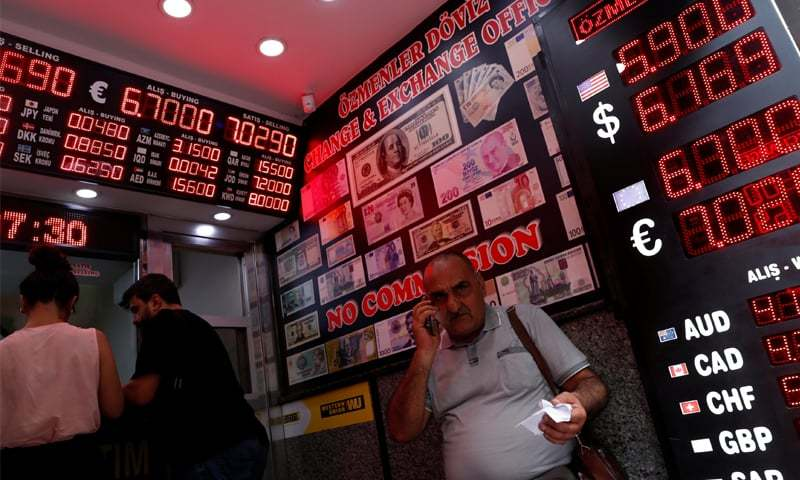 ISTANBUL People change money at a currency exchange office on Friday.—Reuters