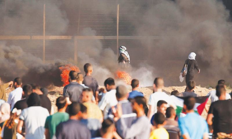 Gaza City: Palestinian protesters ignite a fire in tires during a protest near the border with Israel on Friday.—AFP