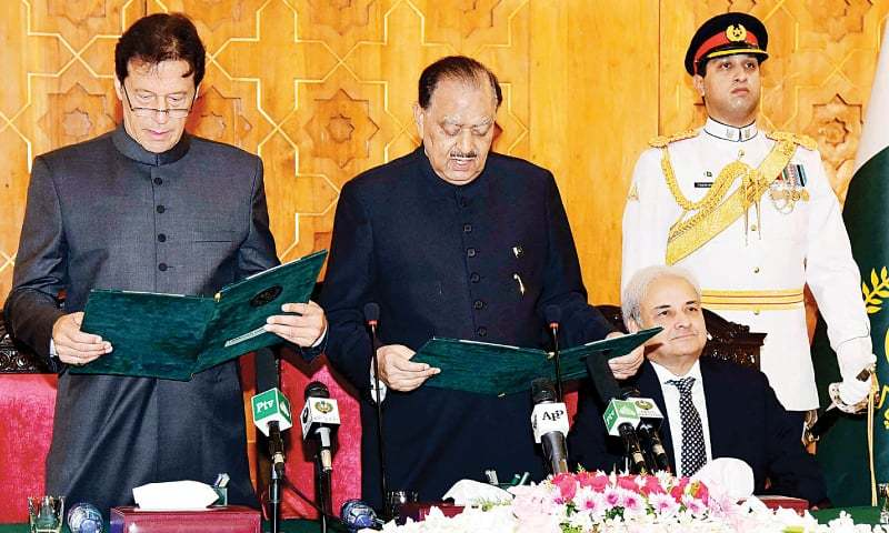ISLAMABAD: Pakistan Tehreek-i-Insaf chairman Imran Khan being administered the oath of prime minister by President Mamnoon Hussain at Awain-i-Sadr on Saturday. Caretaker Prime Minister Nasirul Mulk is also seen. —White Star