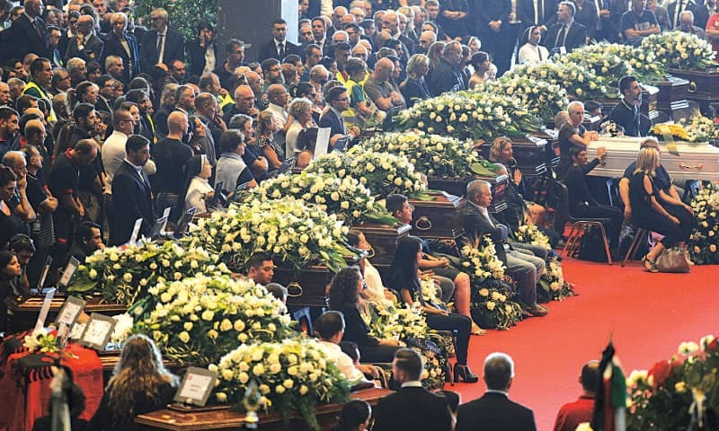 Genoa (Italy): People attend a funeral service for some of the victims of a collapsed highway bridge in Genoa's exhibition centre on Tuesday.—AP