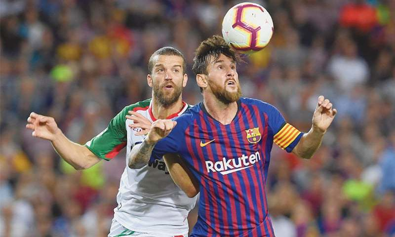BARCELONA: Barcelona's Lionel Messi (R) vies with Deportivo Alaves' Victor Laguardia Cisneros during the La Liga match at the Camp Nou Stadium.—AFP
