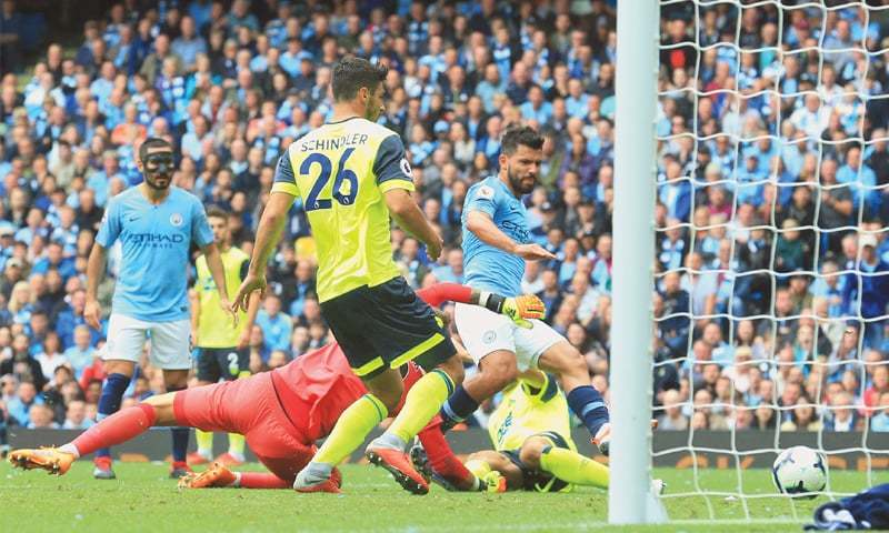 MANCHESTER: Manchester City's Sergio Aguero (R) scores against Huddersfield Town during their English Premier League  at the Etihad Stadium on Sunday.—AFP