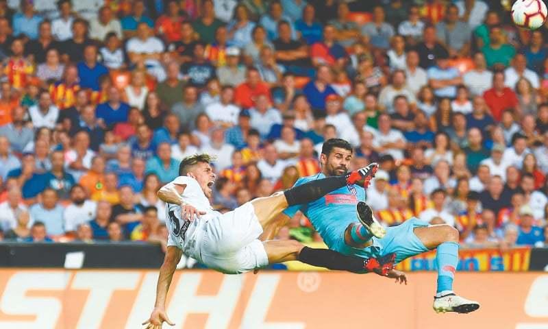 VALENCIA: Atletico Madrid's Diego Costa (R) challenges Gabriel Paulista of Valencia during their La Liga match at the Mestalla Stadium.—AFP