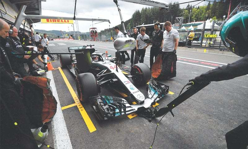 SPA-FRANCORCHAMPS: Technicians work on the car of Mercedes' F1 driver Lewis Hamilton in the pits during the a practice session at the Spa-Francorchamps circuit on Saturday.—AFP