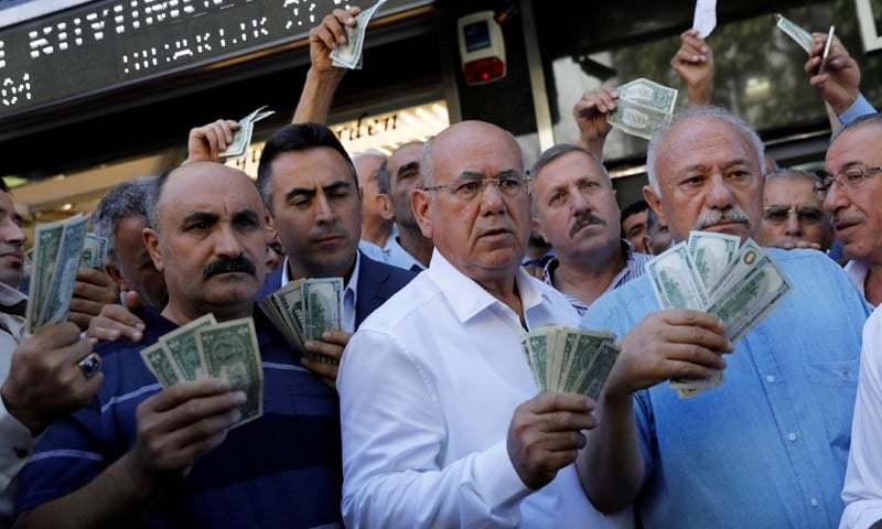 ANKARA: Businessmen holding US dollars stand in front of a currency exchange office.—Reuters