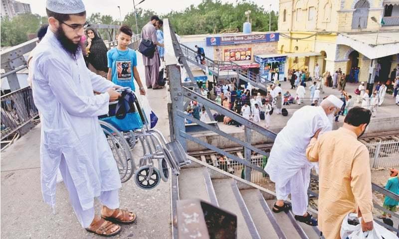 An elderly passenger in a wheelchair being helped down the pedestrian bridge. / Photos by Fahim Siddiqi / White Star