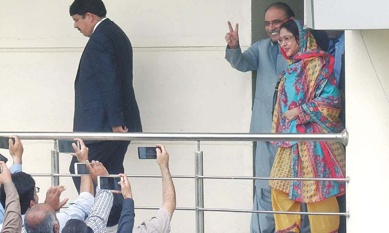 FORMER president Asif Ali Zardari flashes the victory sign while coming out of the FIA's headquarters along with sister Faryal Talpur after recording their statements in an alleged money laundering case on Monday.—Online