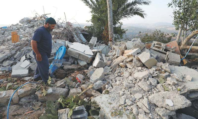 Ramallah (occupied West Bank): A man walks through the rubble of the family house of Palestinian Mohammed Youssef after it was demolished by Israeli troops on Tuesday.—Reuters