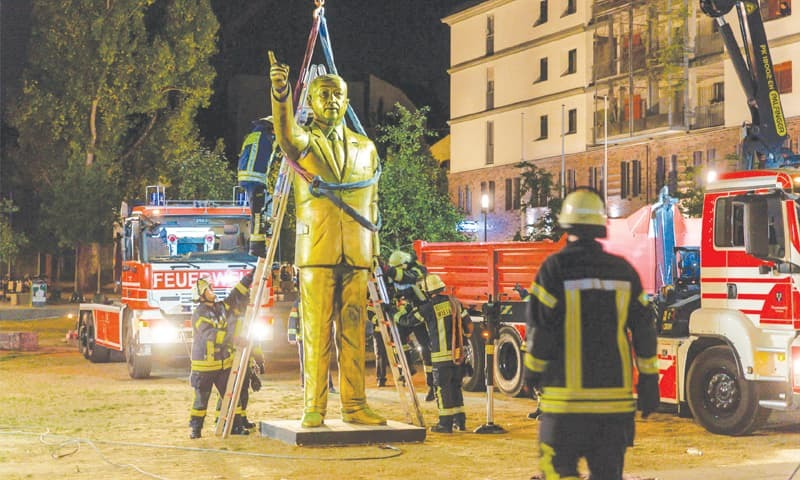 Wiesbaden: Firefighters lift a four-metre tall golden statue of Turkish President Recep Tayyip Erdogan in the early hours of Wednesday. It had been placed on Monday as part of Wiesbaden's Biennale art festival.—AFP