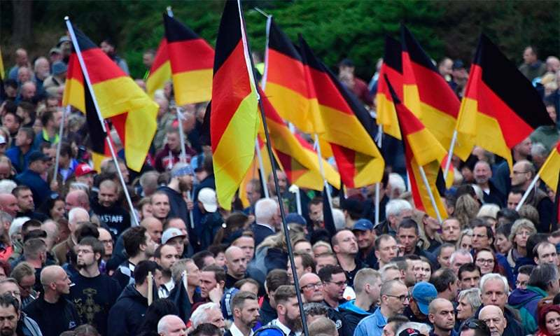 "Demonstrators hold flags of Germany during a protest organised by the right-wing populist ""Pro Chemnitz"" movement, the far-right Alternative for Germany (AfD) party and the anti-Islam Pegida Movement, on September 1 in Chemnitz. ─ AFP"