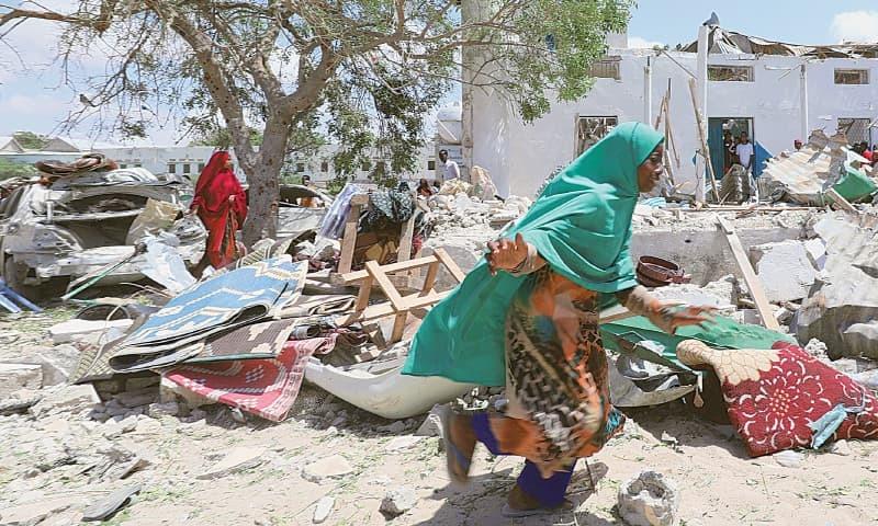MOGADISHU: A woman runs past debris after the suicide attack.—Reuters